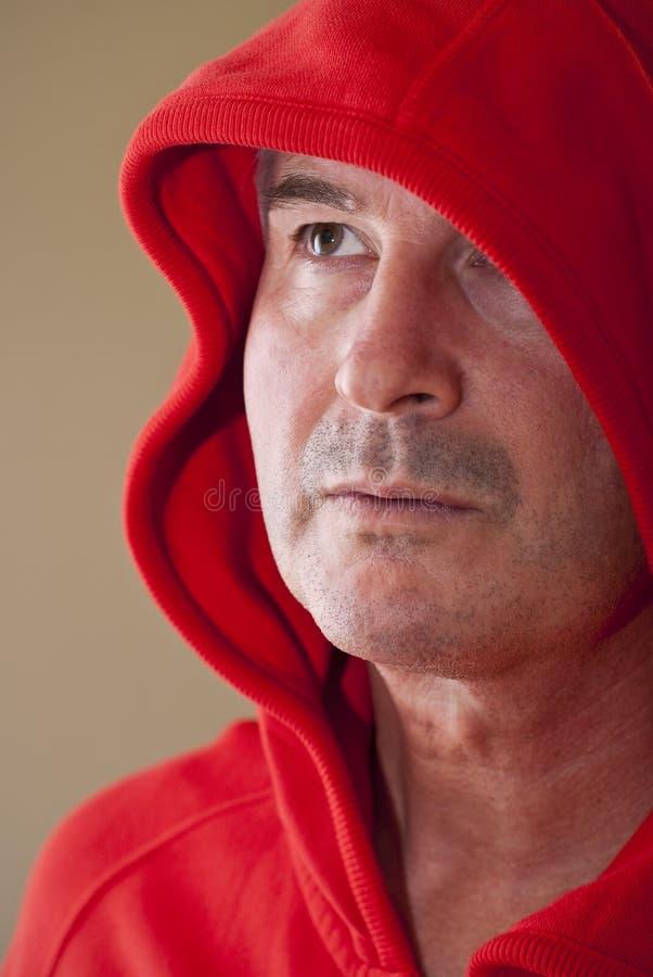 Indivíduo envelhecido médio na capa vermelha fotos de stock royalty free