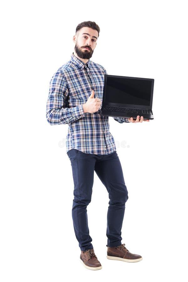 Indivíduo farpado engraçado feliz com a tela aberta do portátil da placa que mostra o polegar acima do gesto imagem de stock