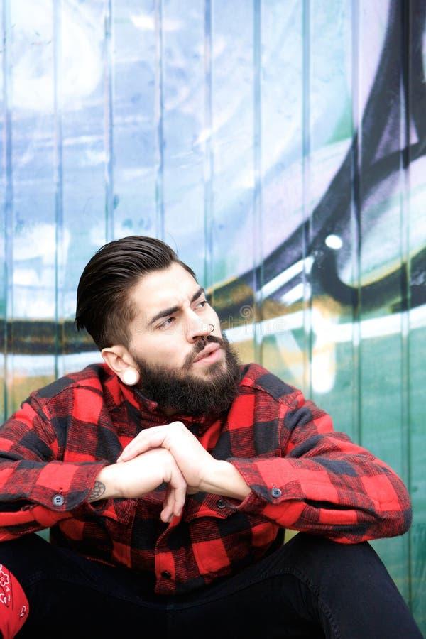 Indivíduo fresco com barba e perfurações que sentam-se fora fotos de stock royalty free