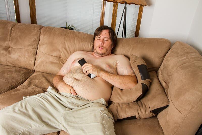 Indivíduo gordo que dorme no sofá fotografia de stock royalty free