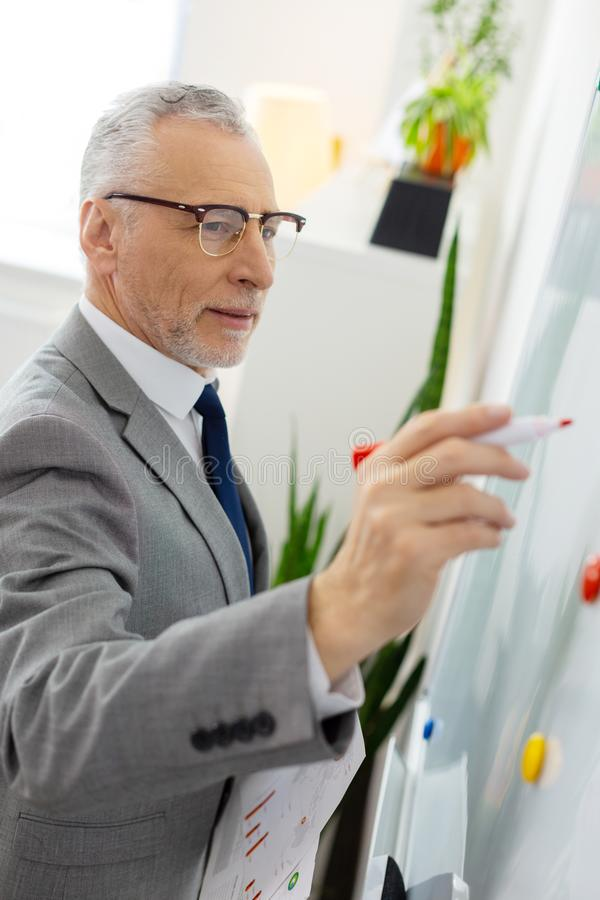 Indivíduo idoso bonito agradável no traje cinzento que redige a informação para trabalhadores fotos de stock royalty free
