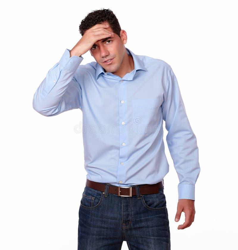 Indivíduo latino-americano cansado com posição da dor de cabeça fotografia de stock royalty free