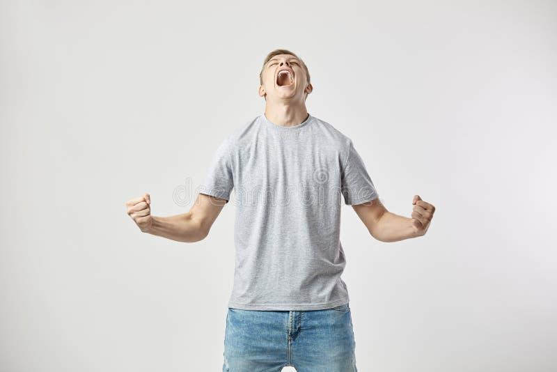 Indivíduo louro vestido em um t-shirt branco e em gritos das calças de brim no fundo branco no estúdio fotos de stock royalty free