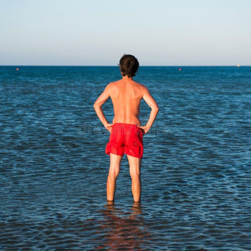 Indivíduo magro que levanta no roupa de banho vermelho na água do mar imagem de stock royalty free