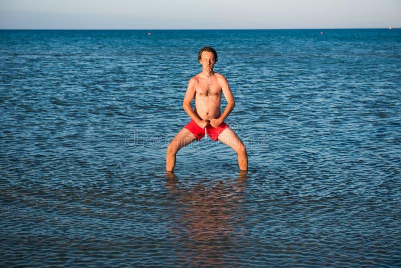 Indivíduo magro que levanta no roupa de banho vermelho na água do mar fotografia de stock