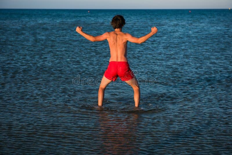 Indivíduo magro que levanta no roupa de banho vermelho na água do mar fotos de stock royalty free