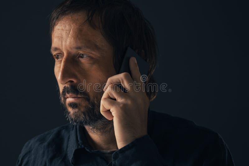 Indivíduo melancólico desolado amargo que fala no telefone celular foto de stock