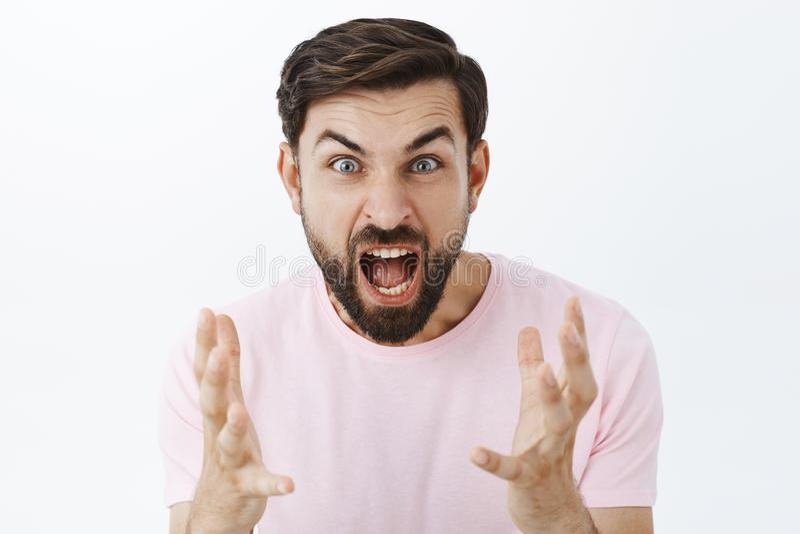 Indivíduo mijado que grita da raiva e do ódio durante o argumento Retrato do homem caucasiano exercido pressão sobre insultado co fotografia de stock
