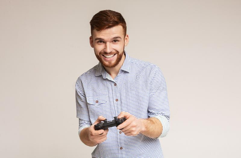 Indivíduo milenar entusiasmado que joga jogos de vídeo com jpystick fotos de stock