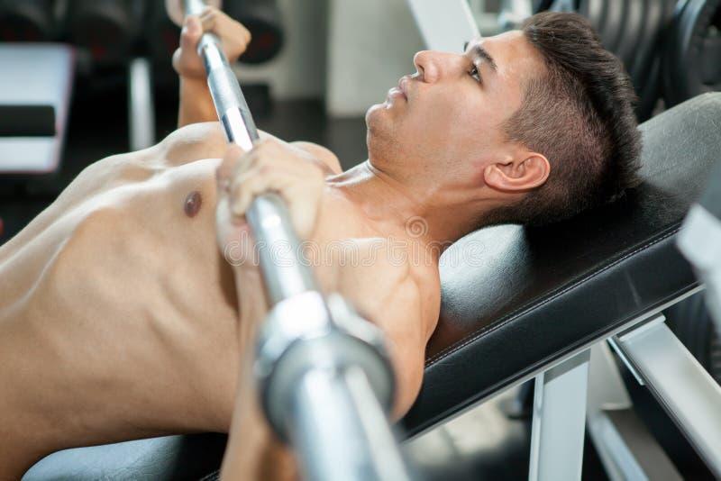 Indivíduo muscular do halterofilista que faz o peso de levantamento ao dar certo fotografia de stock royalty free
