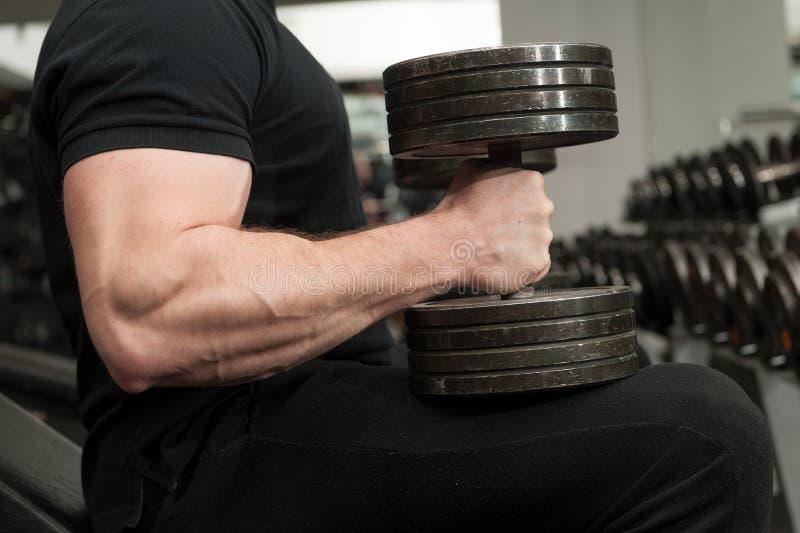 Indivíduo muscular do halterofilista que guarda pesos pretos grandes do ferro em um gym O homem com mão grande muscles dar certo  foto de stock royalty free