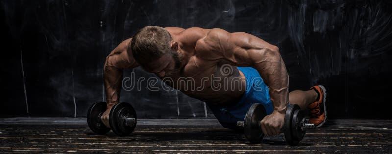 Indivíduo muscular do halterofilista sobre o fundo escuro foto de stock royalty free