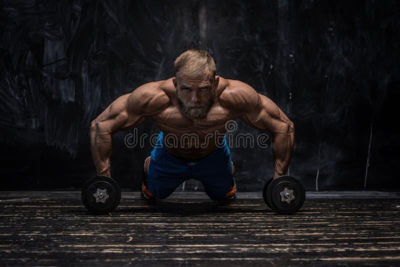 Indivíduo muscular do halterofilista sobre o fundo escuro foto de stock