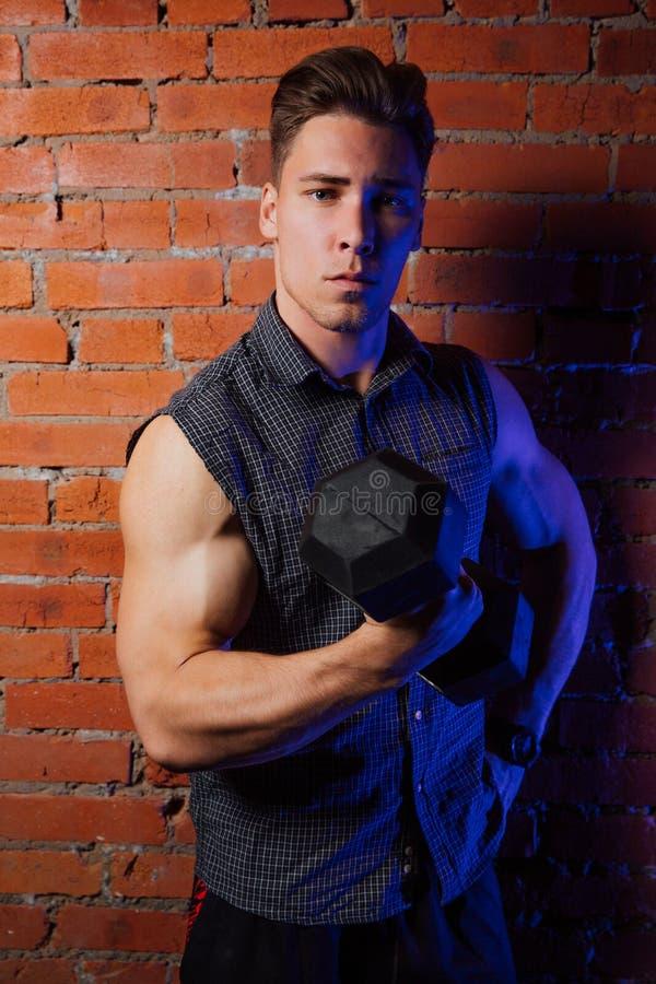 Indivíduo muscular que faz exercícios com peso contra uma parede de tijolo foto de stock royalty free