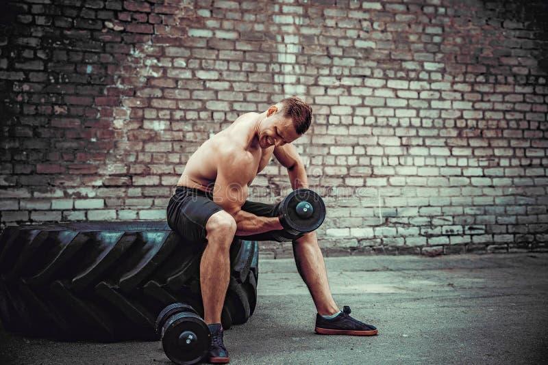 Indivíduo muscular que faz exercícios com peso contra uma parede de tijolo fotos de stock royalty free