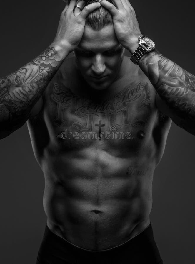 Indivíduo muscular Tattooed que guarda sua cabeça fotos de stock