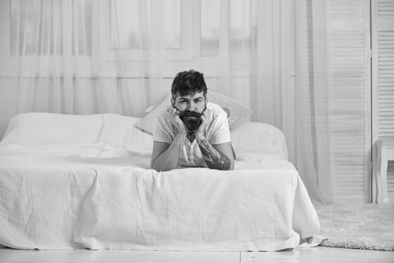 Indivíduo na cara calma que coloca na borda da cama nas folhas brancas Equipe a colocação na cama, cortinas brancas no fundo Quar imagens de stock