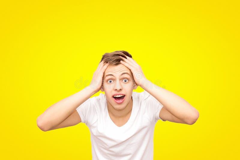 Indivíduo no branco em um t-shirt branco que guarda sua cabeça, isolada em um fundo amarelo fotos de stock royalty free