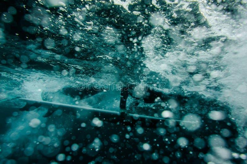 Indivíduo no roupa de banho preto que flui abaixo de guardar um mergulho da placa de ressaca sob a onda foto de stock
