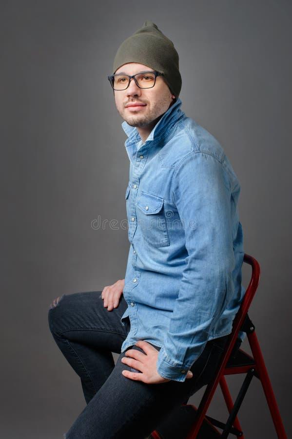 Indivíduo novo à moda em uma camisa das calças de brim e em uns vidros vestindo em um fundo cinzento que está na escada fotografia de stock