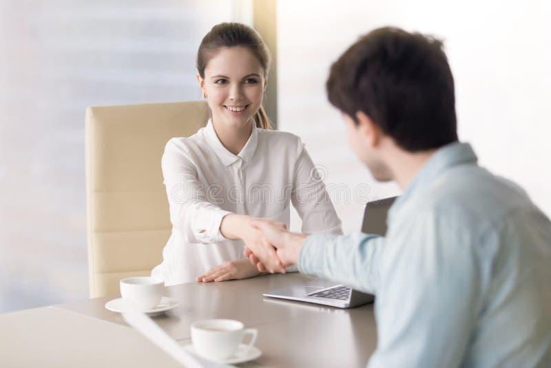 Indivíduo novo aceitado para um trabalho e um aperto de mão fêmea do gerente foto de stock