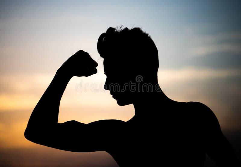 Indivíduo novo atlético forte Silhueta bonita contra o sol de ajuste fotografia de stock royalty free