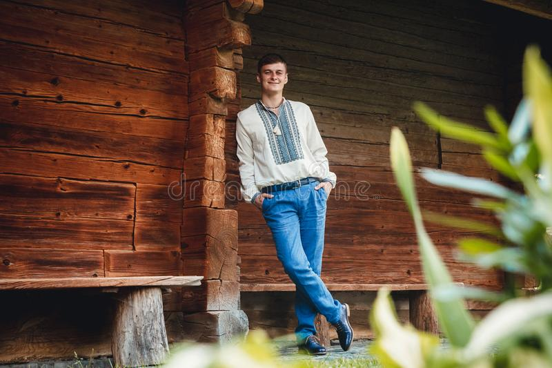 Indivíduo novo bonito em uma camisa bordada no fundo de uma casa de madeira foto de stock royalty free