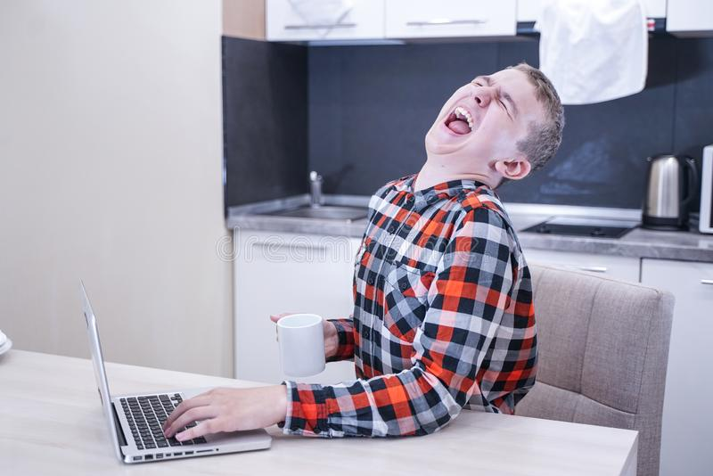 Indivíduo novo bonito que senta-se em uma camisa de manta com um portátil e um trabalho, estudando em casa apenas imagens de stock