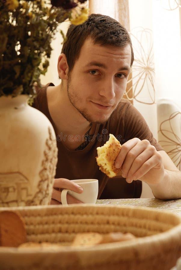 Indivíduo novo com chá e bolo na cozinha fotografia de stock royalty free