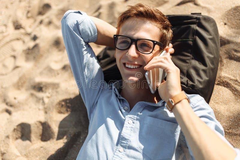 Indivíduo novo com os vidros, encontrando-se na praia na areia, e falando no telefone, trabalho nas férias, apropriadas para anun imagens de stock