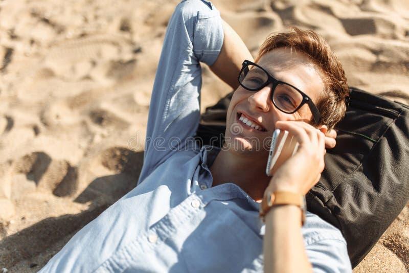 Indivíduo novo com os vidros, encontrando-se na praia na areia, e falando no telefone, trabalho nas férias, apropriadas para anun imagem de stock royalty free