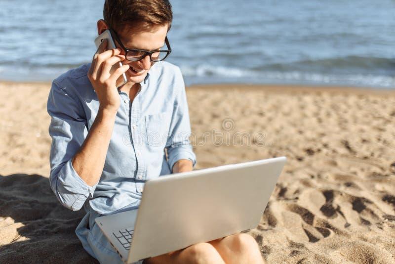 Indivíduo novo com os vidros, trabalhando em seu portátil e falando no telefone na praia, trabalhando nas férias, apropriadas par foto de stock