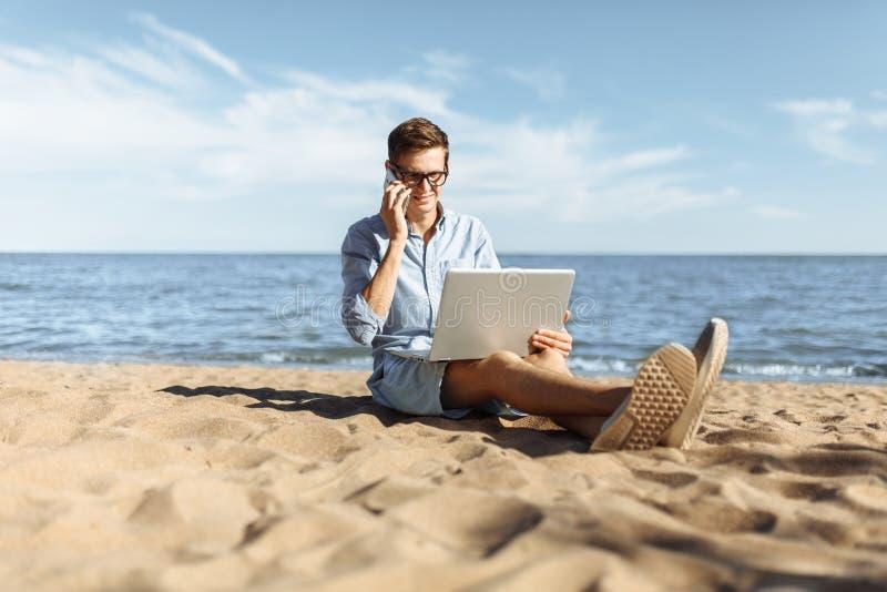 Indivíduo novo com os vidros, trabalhando em seu portátil e falando no telefone na praia, trabalhando nas férias, apropriadas par fotografia de stock royalty free