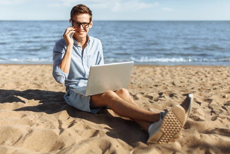 Indivíduo novo com os vidros, trabalhando em seu portátil e falando no telefone na praia, trabalhando nas férias, apropriadas par fotos de stock royalty free