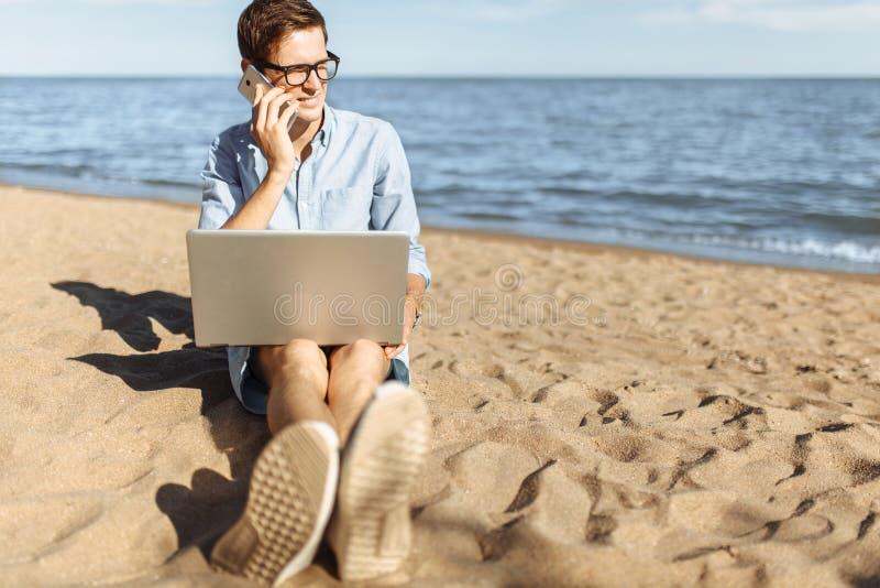 Indivíduo novo com os vidros, trabalhando em seu portátil e falando no telefone na praia, trabalhando nas férias, apropriadas par fotos de stock