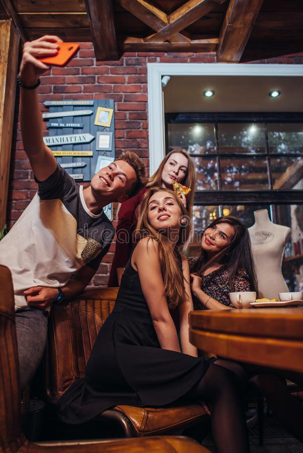 Indivíduo novo considerável que toma o selfie com um grupo de meninas bonitas que têm o jantar no restaurante na moda imagens de stock royalty free