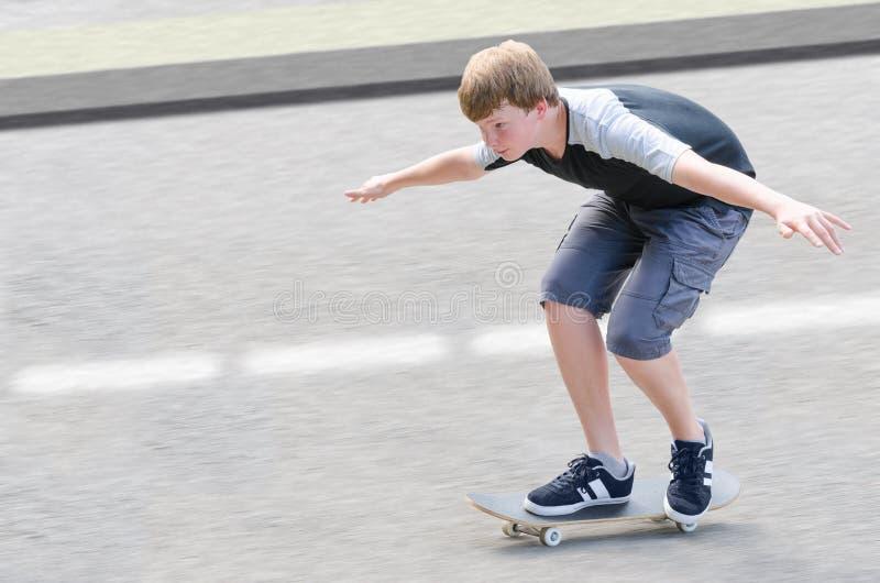 Indivíduo novo do adolescente do skater no movimento que move sobre o skate foto de stock