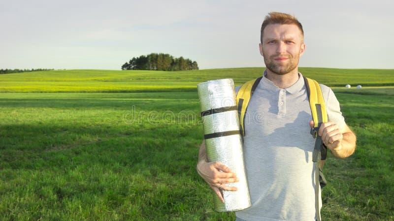 Indivíduo novo do turista com um tapete e uma trouxa contra um prado verde em um dia de verão imagem de stock royalty free