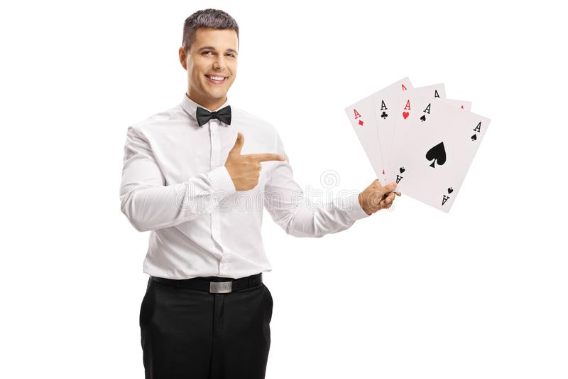 Indivíduo novo em um tux que guarda cartões de jogo e apontar imagens de stock