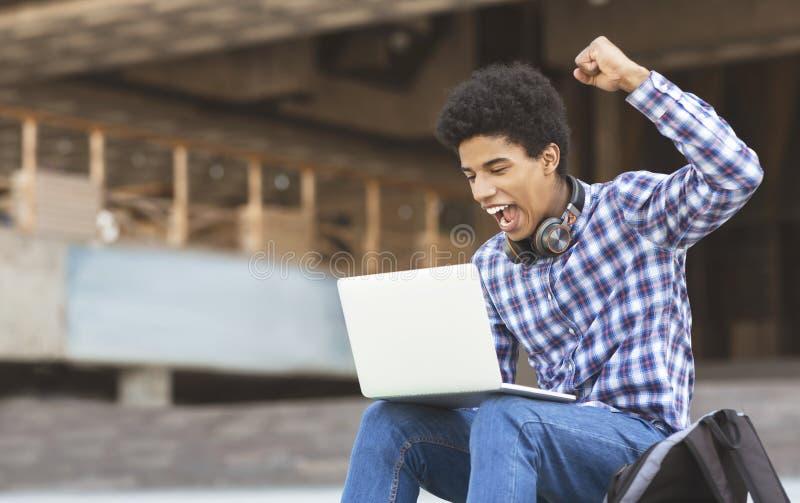 Indivíduo novo entusiasmado que comemora a vitória com portátil fora imagem de stock