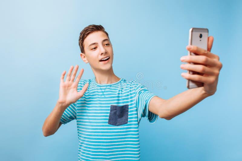 Indivíduo novo que fala o bate-papo video em linha, no telefone no estúdio foto de stock