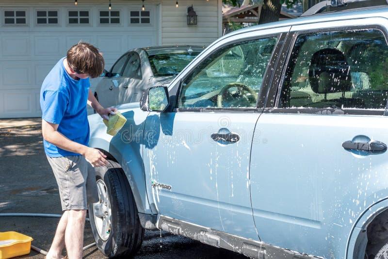 Indivíduo novo que lava SUV na entrada de automóveis em um dia de verão imagem de stock