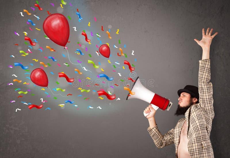 Indivíduo novo que tem o divertimento, gritaria no megafone com balões imagens de stock