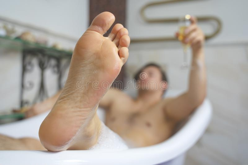 Indivíduo novo que tem um banho da espuma que relaxa Champagne bebendo Foco no pé foto de stock royalty free