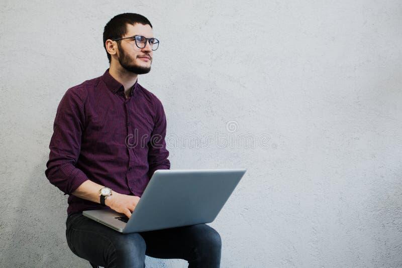 Indivíduo pensativo novo que usa o portátil, vidros vestindo no fundo do branco fotografia de stock royalty free