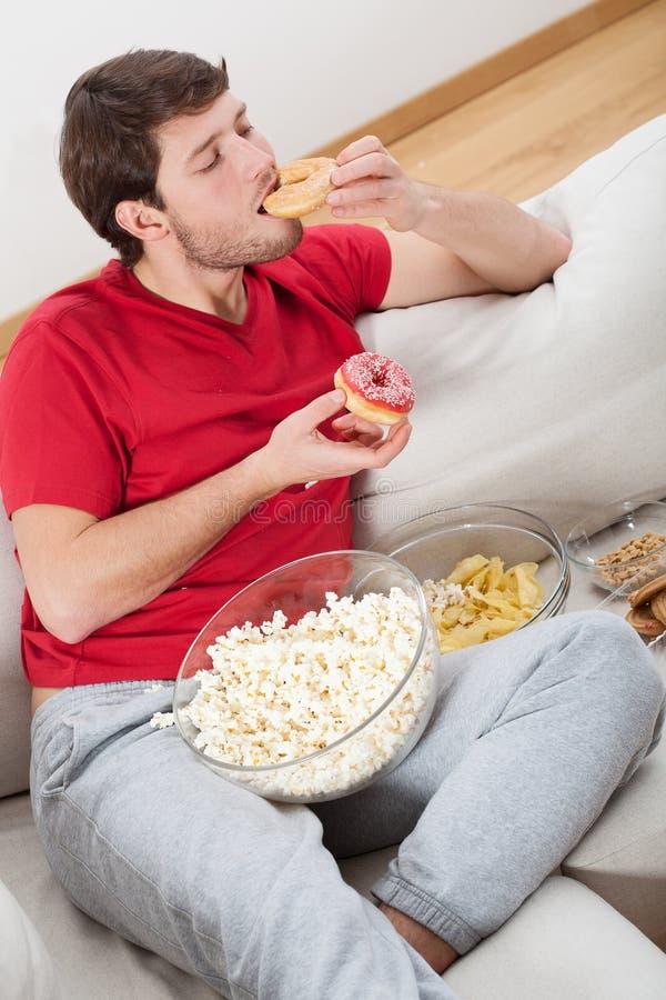 Indivíduo preguiçoso em um sofá com alimento foto de stock