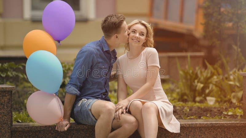 Indivíduo que beija a amiga amado no mordente, mantendo balões de ar coloridos disponivéis fotos de stock royalty free