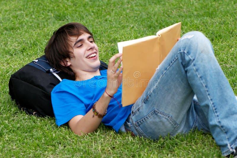 Indivíduo que coloca na grama e que lê um livro imagem de stock royalty free