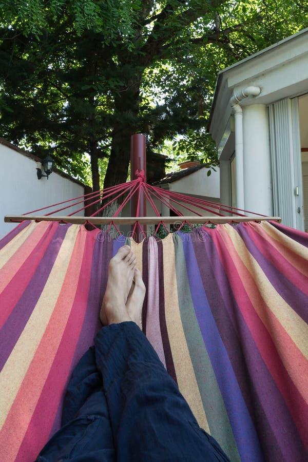 Indivíduo que encontra-se para baixo em uma rede colorida que descansa com os pés descalços Pés cruzados de um homem que toma a s fotografia de stock royalty free