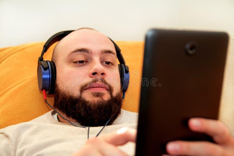 Indivíduo que escuta a música em casa em sua tabuleta fotos de stock royalty free
